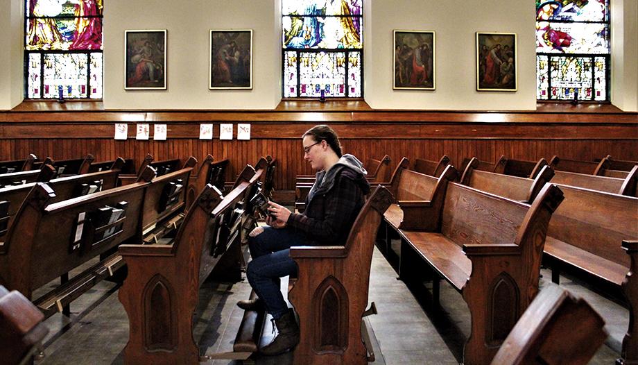 Chica joven leyendo un libro sentada dentro de una Iglesia.